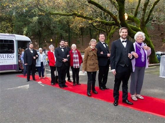 A group of people walking along a red carpet