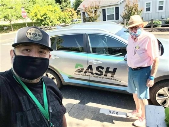 Two people wearing masks with DASH car.