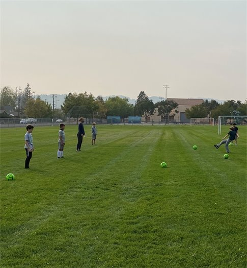Image of kid kicking soccer ball to other children