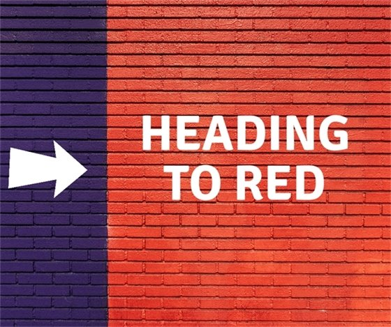 Red brick wall with text that reads Heading to Red